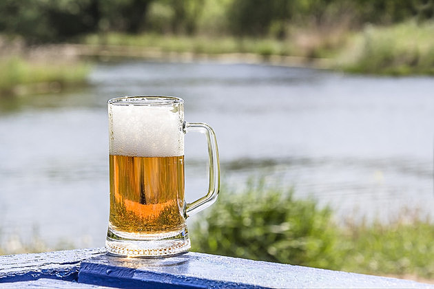 Mug of frothy beer on the table near lake